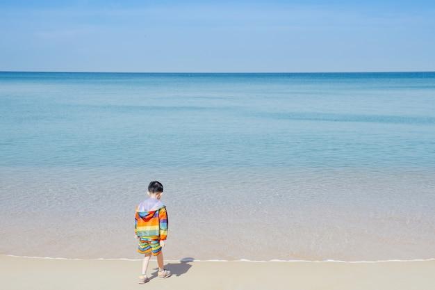 Azjatycki chłopiec chodzi na plaży outdoors morze i niebieskie niebo