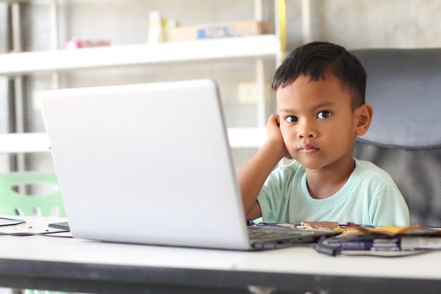 Azjatycki chłopiec dziecko siedzi przy stole z laptopem i przygotowuje się do szkoły. koncepcja edukacji online. badanie lekcji na lekcjach konferencji wideo online.