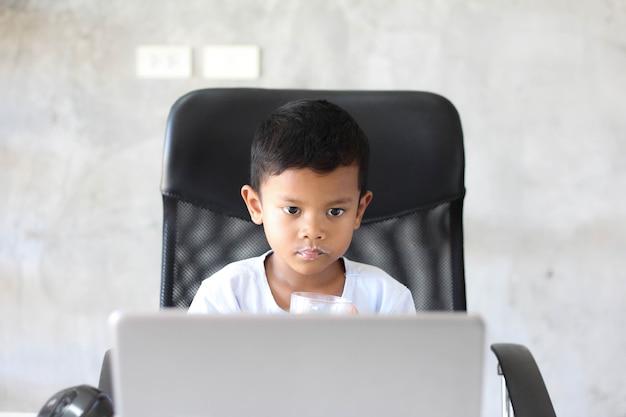 Azjatycki chłopiec dziecko siedzi przy stole z laptopem i przygotowuje się do szkoły