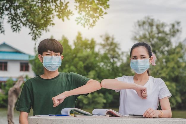 Azjatycki chłopiec i dziewczynka wracają do szkoły, nosząc maskę i uścisk dłoni, utrzymują nowy normalny bez dotykania dystans społeczny