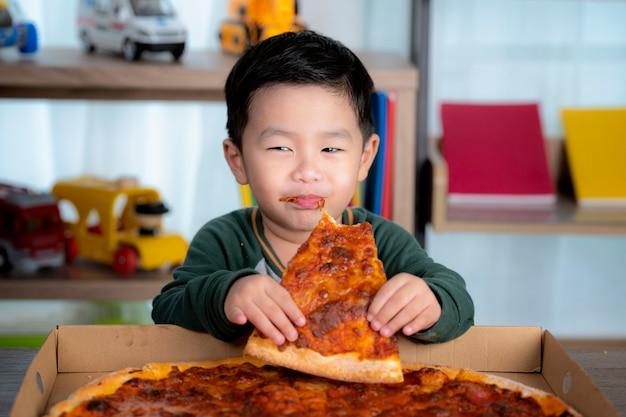 Azjatycki chłopiec jedzenie pizzy i pudełko po pizzy postawione na stole.