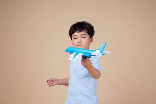 Azjatycki chłopiec jest ekscytujący w podróży samolotem zabawka na beżowym tle