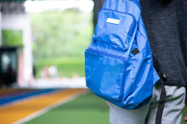 Azjatycki chłopiec, który idzie do szkoły ze swoim szkolnym plecakiem.