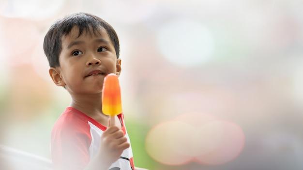 Azjatycki chłopiec łasowania lody w zamazanym tle