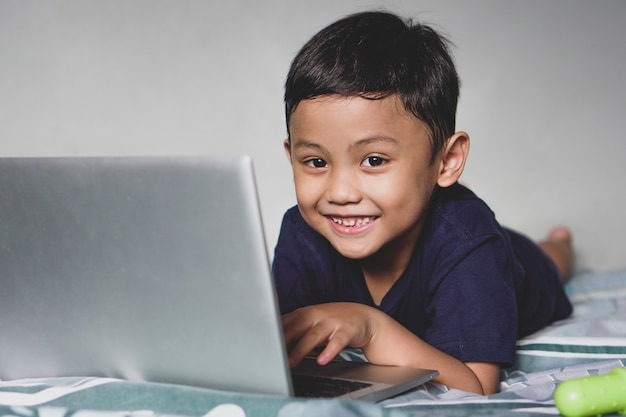 Azjatycki chłopiec leżący na łóżku używający laptopa z uśmiechem patrząc w przyszłość