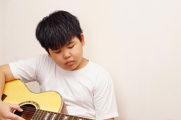 Azjatycki chłopiec lubi grać na gitarze akustycznej. białe tło.