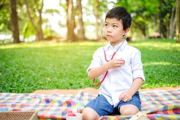 Azjatycki chłopiec odtwórz doktor w parku przyrody