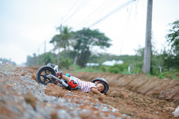 Azjatycki chłopiec około 2 lat jedzie rowerem równowagi dziecka i spada