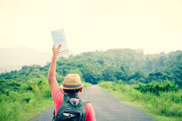 Azjatycki chłopiec podróżujący na łonie natury niosący aparat z mapą, aby zbadać trasę