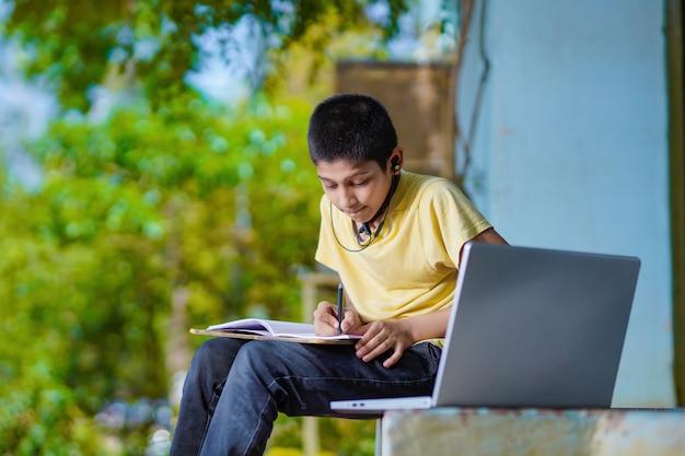 Azjatycki chłopiec przy użyciu komputera przenośnego do nauki online homeschooling podczas kwarantanny domowej. nauczanie domowe, nauka online, kwarantanna domowa, nauka online, koronawirus lub koncepcja technologii edukacyjnej
