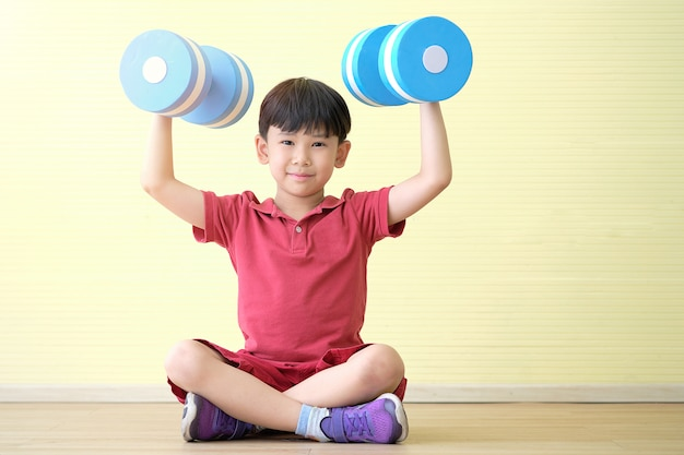 Azjatycki chłopiec siedzi i hantle podnoszenia obiema rękami i twarzą uśmiecha się