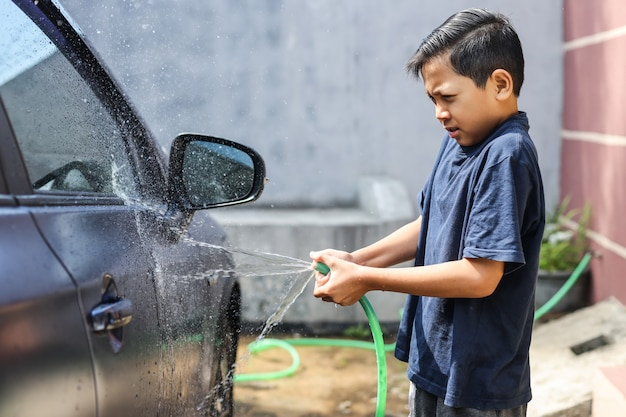 Azjatycki chłopiec spryskujący wodę z węża do mycia samochodu