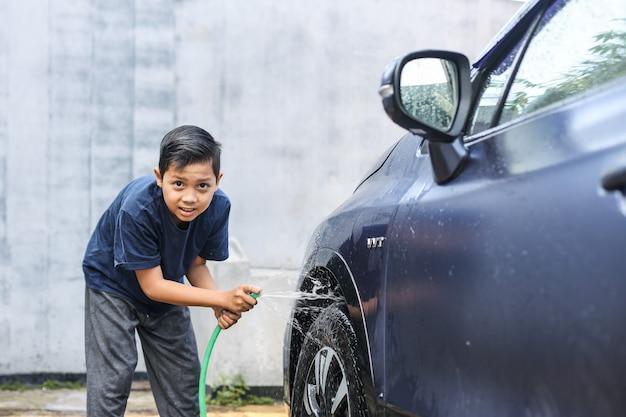 Azjatycki chłopiec spryskujący wodę z węża na opony samochodu