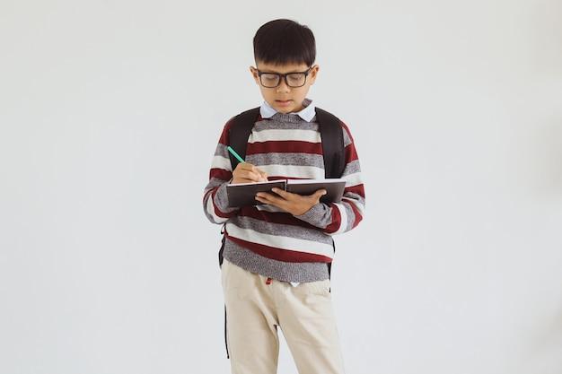 Azjatycki chłopiec szkolny piszący w książce stojący