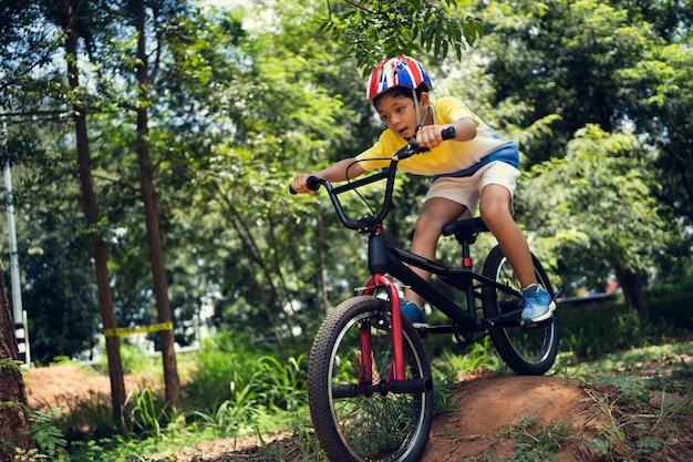 Azjatycki chłopiec trenuje do szczęśliwego kolarstwa górskiego.