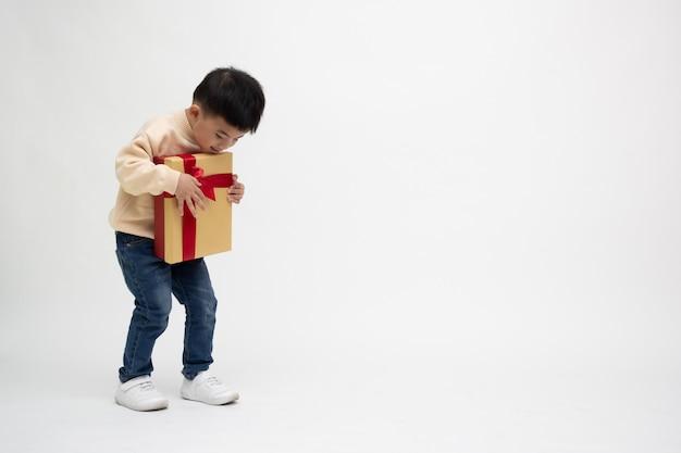 Azjatycki Chłopiec Trzyma Złoto Pudełko Na Białym Tle. Koncepcja Nowego Roku I Bożego Narodzenia Premium Zdjęcia