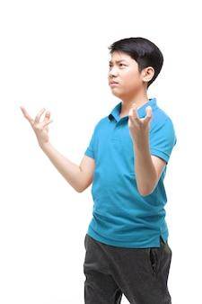 Azjatycki chłopiec ubrany w niebieską koszulę wykonuje jakiś gest.