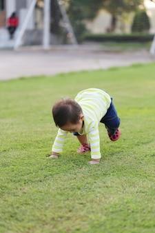 Azjatycki chłopiec uczy się chodzić w ogrodzie.