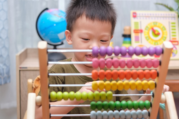 Azjatycki chłopiec używa liczydła z koralikami, aby nauczyć się liczyć