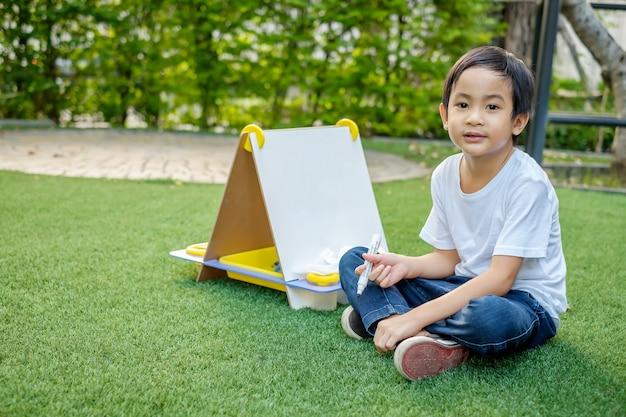 Azjatycki chłopiec w białej koszulce i dżinsach siedzi na trawniku i pisze na białej tablicy.