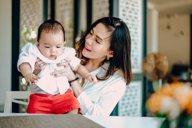 Azjatycki chłopiec w białej koszuli bawi się z matką