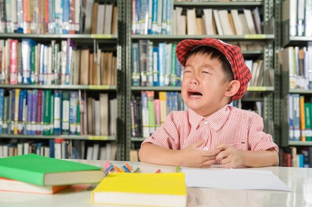 Azjatycki chłopiec w bibliotece pokój szkoły