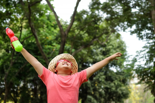Azjatycki chłopiec w czerwonych okularach, w kapeluszu, trzymając pistolet, świeża woda, stojący, rozłożył ręce w ogrodzie