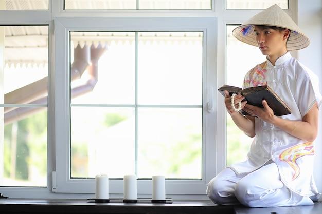 Azjatycki chłopiec w kimonie czytający starą książkę siedzącą przy oknie