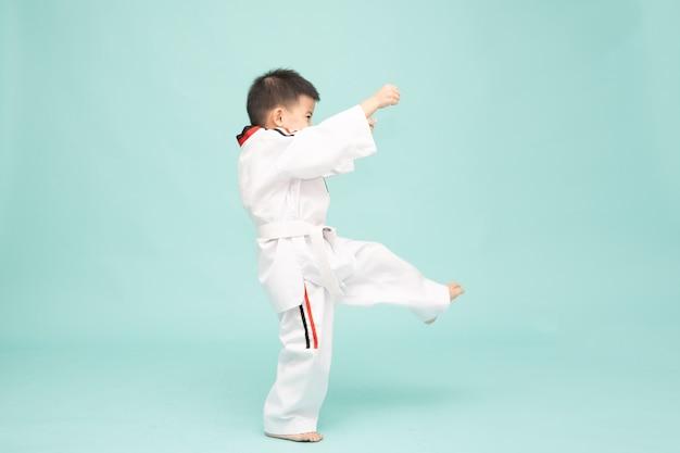 Azjatycki chłopiec w kostiumie taekwondo wykonujący ruchy sztuk walki na białym tle na zielonym tle 3 lata