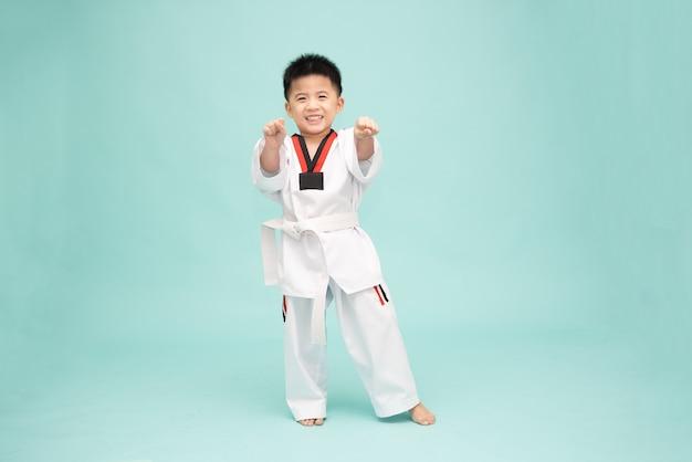 Azjatycki chłopiec w kostiumie taekwondo wykonujący ruchy sztuk walki na białym tle na zielonym tle