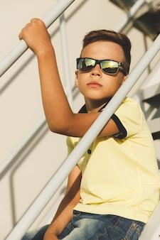 Azjatycki chłopiec w okularach przeciwsłonecznych na schodach w żółtej koszulce i dżinsach