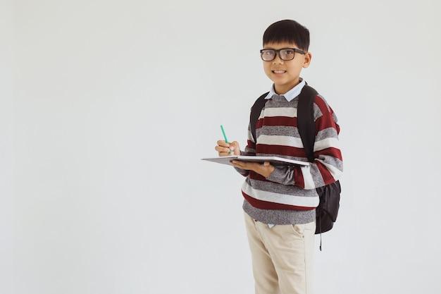 Azjatycki chłopiec w szkole pisze w książce, stojąc i patrząc w kamerę