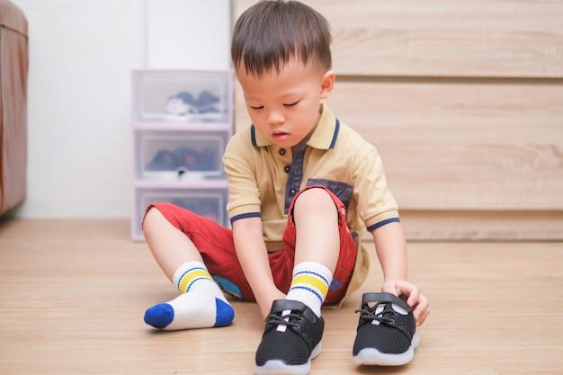 Azjatycki chłopiec w wieku 2-3 lat siedzi i koncentruje się na zakładaniu swoich czarnych butów / trampek