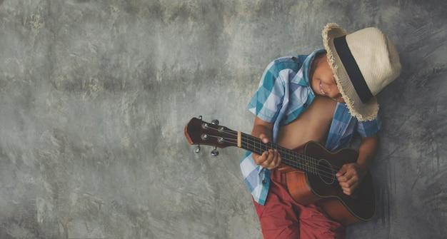 Azjatycki chłopiec w wieku 5-6 odtwórz ukulele fajny gest namiętna miłość w muzyce pustej przestrzeni