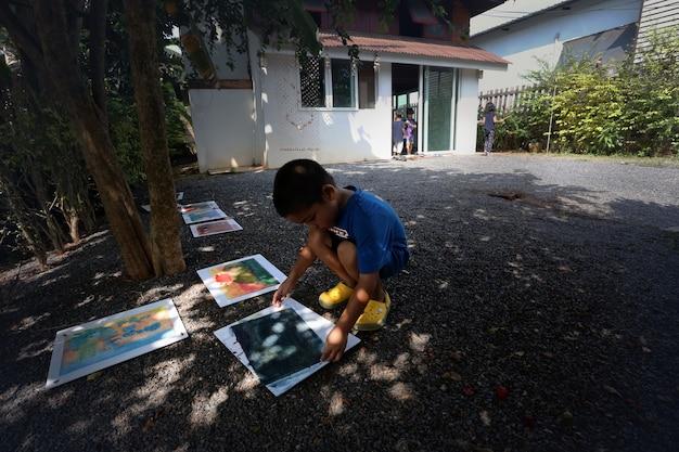 Azjatycki chłopiec ze swoim malowaniem działa w domu, uczeń domu i koncepcja edukacji waldorf.