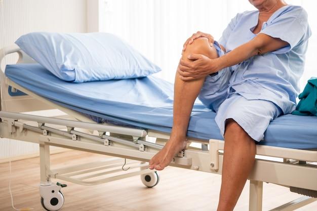 Azjatycki cierpliwy mężczyzna czuje ból na jego kolanie przy sala szpitalną.
