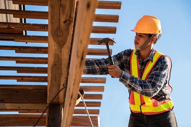 Azjatycki cieśla dekarz pracujący na konstrukcji dachu na budowie, dekarz
