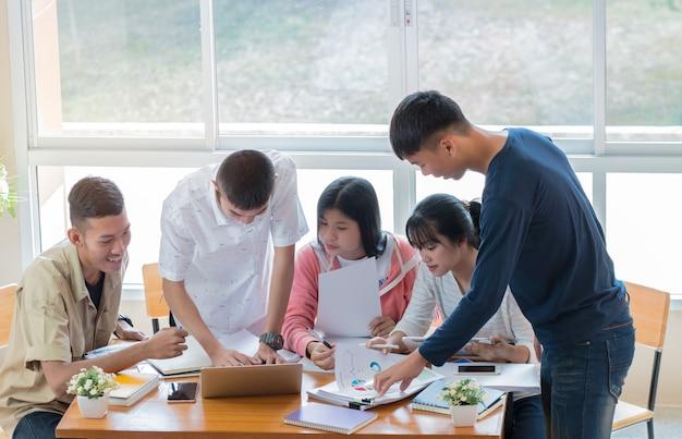 Azjatycki college grup studentów za pomocą laptopa