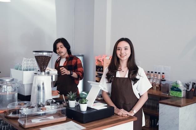 Azjatycki cukierniany właściciel ono uśmiecha się kamera