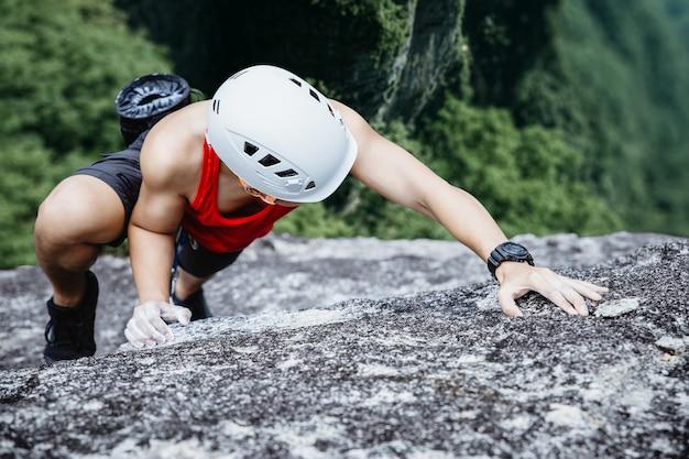 Azjatycki człowiek alpinista w czarnych spodniach, wspinaczka na klif.