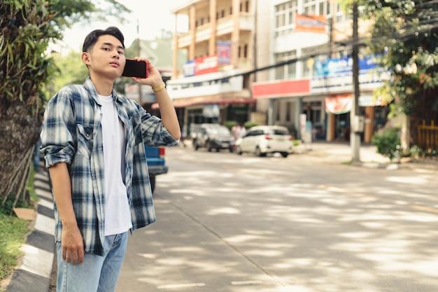 Azjatycki człowiek czeka na taksówkę uber
