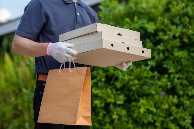 Azjatycki człowiek dostawy pracownika w niebieską czapkę t-shirt jednolity maska rękawiczki trzymać pakiet papieru rzemiosła na jedzenie na wynos. usługa kwarantanny pandemiczny wirus koronawirusa [covid-19]