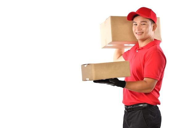 Azjatycki człowiek dostawy w czerwonym mundurze z paczką karton na białym tle