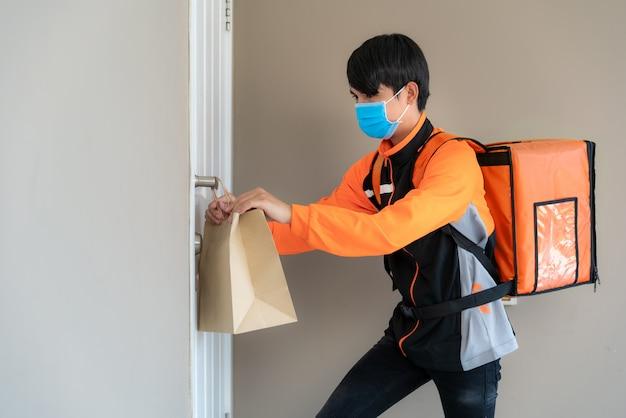 Azjatycki człowiek dostawy wysyła torbę z jedzeniem do klamki drzwi dla kontaktu bezdotykowego lub kontaktu bez kierowcy z domu przed domem w celu zdystansowania się od ryzyka infekcji.