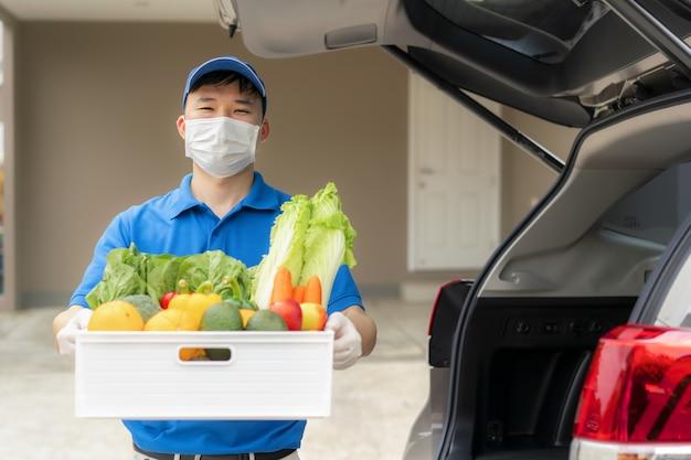 Azjatycki człowiek dostawy z pudełkiem artykułów spożywczych