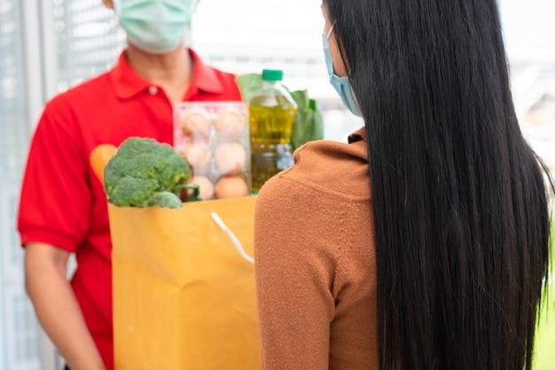 Azjatycki człowiek dostawy z supermarketu w masce i trzymając worek świeżej żywności za dawanie klientom w domu.