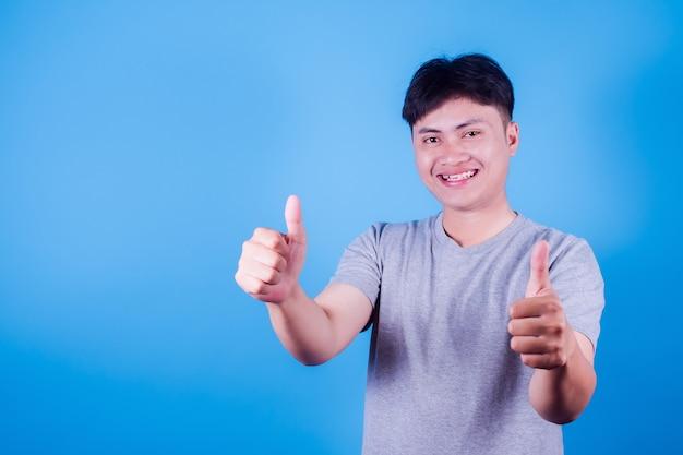 Azjatycki człowiek facet sobie uśmiecha się do kamery, pokazując kciuk do góry. portret pół ciała na niebieskim tle.