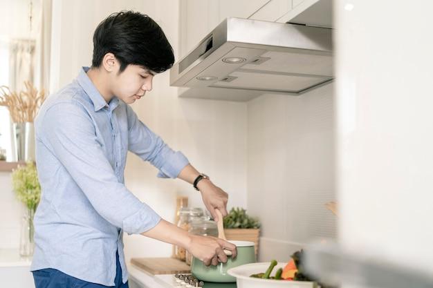 Azjatycki człowiek gotuje w domowej kuchni