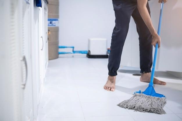 Azjatycki człowiek inspekcji personelu sprzątającego w kuchni, rozmyta łazienka