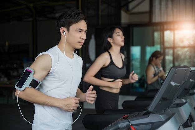Azjatycki człowiek mięśni działa na bieżni